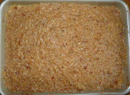 Gluten-free German chocolate cake with coconut-pecan icing in baking pan.