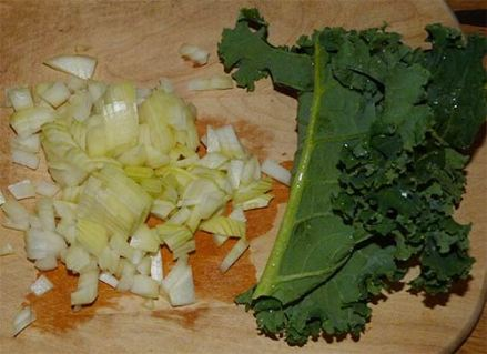 Chopped onions and a kale leave on a cutting board.