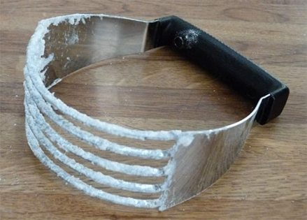 Metal pastry blender on countertop covered with flour and shortening.