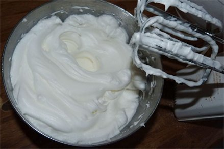 Metal mixing bowl containing whipped egg whites.