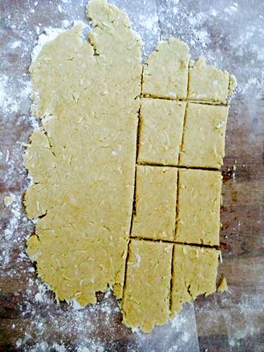 Gluten-free cracker dough rolled out on wax paper with some of the crackers cut out of it.