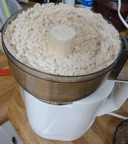 Food processor with flour and coconut mixture inside.
