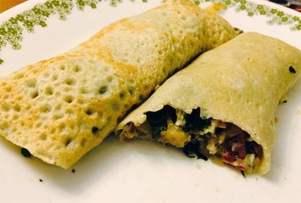 Two rolled up gluten-free crepes with vegetable filling on a plate.