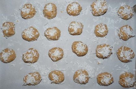 About two dozen cookie dough balls covered with coconut on parchment paper and baking sheet.