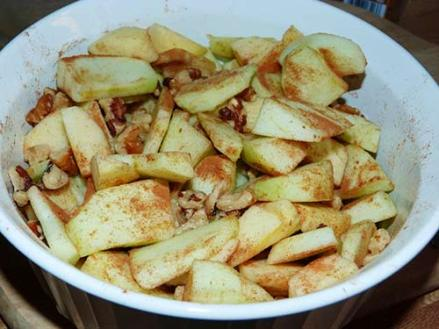 Casserole dish containing sliced apples, cinnamon and walnuts.