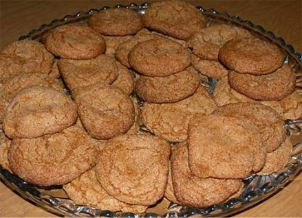Cookies piled up on a glass serving tray.