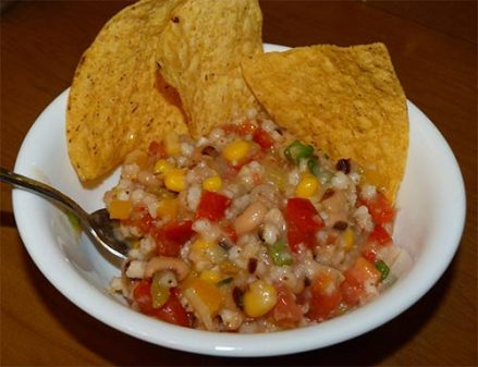 White serving bowl containing sorghum caviar and three tortilla chips.