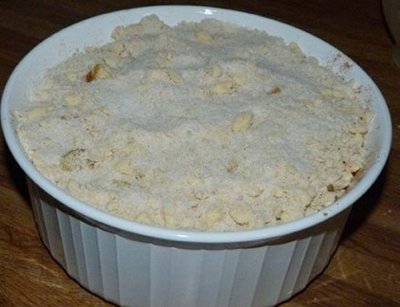 White circular casserole dish containing sliced apples with crumbly topping added to the top.