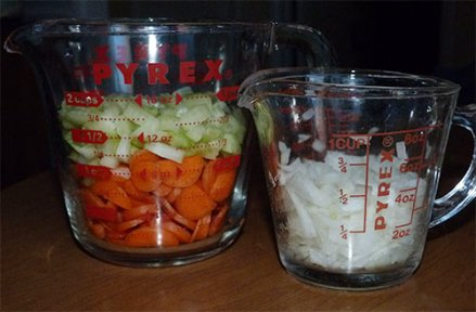 Chopped carrots, celery and onion in glass measuring cups.