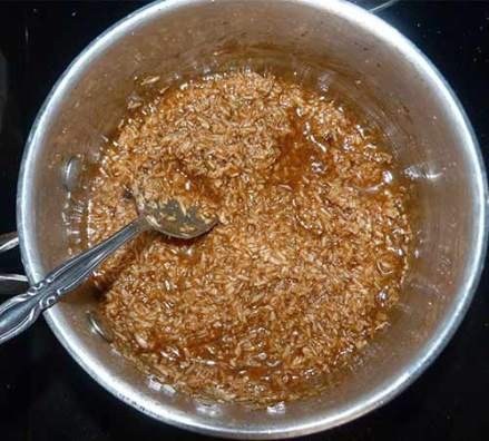 Shredded coconut added to caramel mixture in sauce pan on stove.