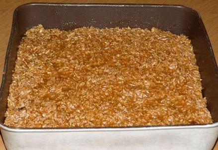 Coconut caramel topping added to cake in pan.
