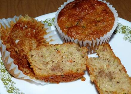 Gluten-free zucchini carrot muffin broken open on a dessert plate.