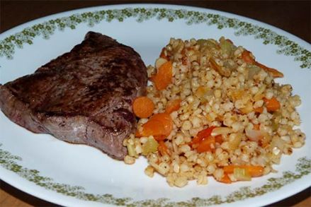 Sorghum pilaf on a plate with a steak