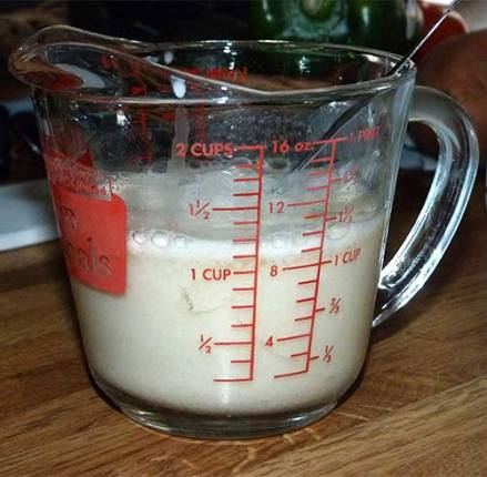 Glass measuring cup containing almond milk and vinegar mix.