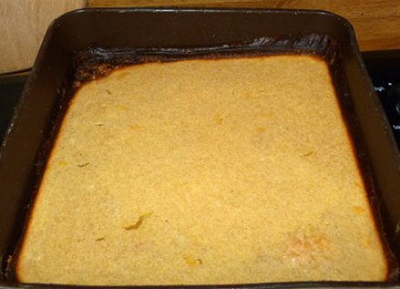 Baked lemon squares in baking pan, edges overcooked.