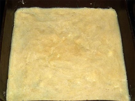 Gluten-free crust dough for lemon squares pressed down in the bottom of a square baking pan.