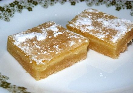 Two gluten-free lemon squares on a dessert plate.