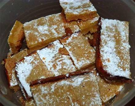 Gluten-free lemons squares in bowl, sprinkled with confectioner's sugar.