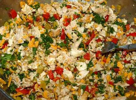 Chicken mixed with vegetables and sorghum in a large bowl.