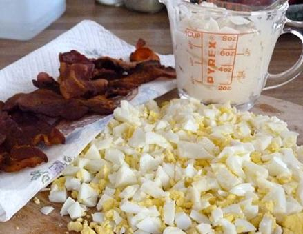 Cooked bacon and chopped up hard boiled eggs on a cutting board with cup of mayonnaise sitting behind.