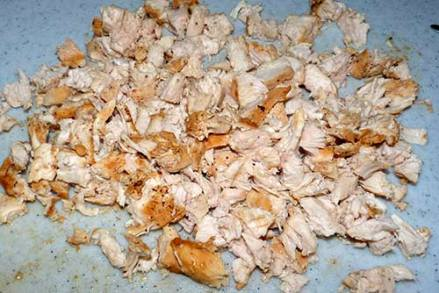 Chopped up cooked chicken breast on a cutting board.