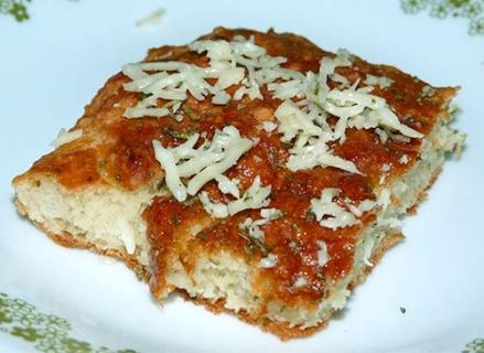 Slice of gluten-free rosemary focaccia on a plate, golden brown on top with melted Parmesan cheese.