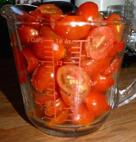 Two-cup glass measuring cup filled to brim with grape tomato halves.