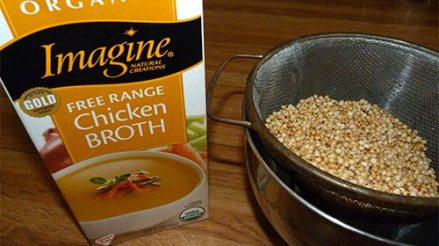 Package of chicken broth next to rinsed sorghum grains in a strainer.