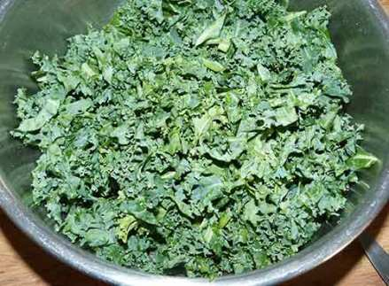 Metal bowl containing chopped up kale.