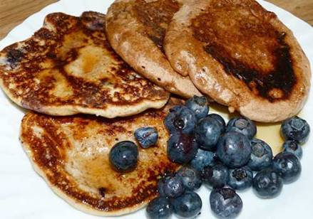 Four gluten free pancakes on a white plate with syrup and fresh blueberries.