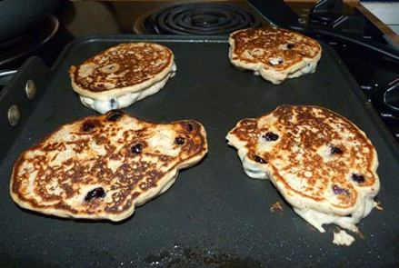 Four blutberry pancakes cooking on a griddle.