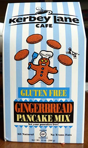 Front of box of Kerbey Lane Gingerbread Pancake Mix. It has cartoon image of a gingerbread man flipping pancakes.