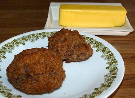 Two buckwheat sorghum biscuits on a small plate with a butter dish and a stick of butter in the background.