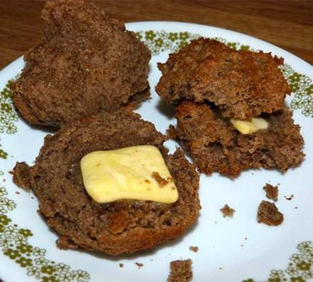 Two buckwheat sorghum biscuits cut open with butter on a small plate.