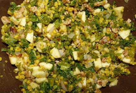 Sorghum salad with apples and walnuts added in a brown mixing bowl.